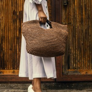 woman-holding-brown-bag-near-brown-wooden-surfac-1942879